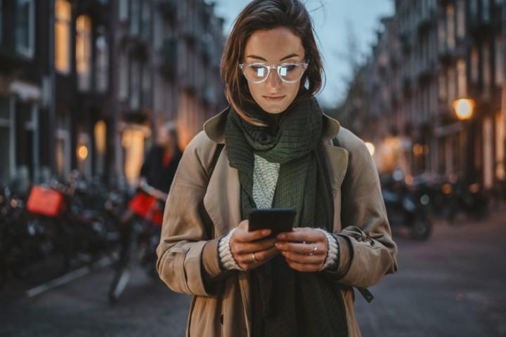 Nainen käyttää puhelinta kadulla.