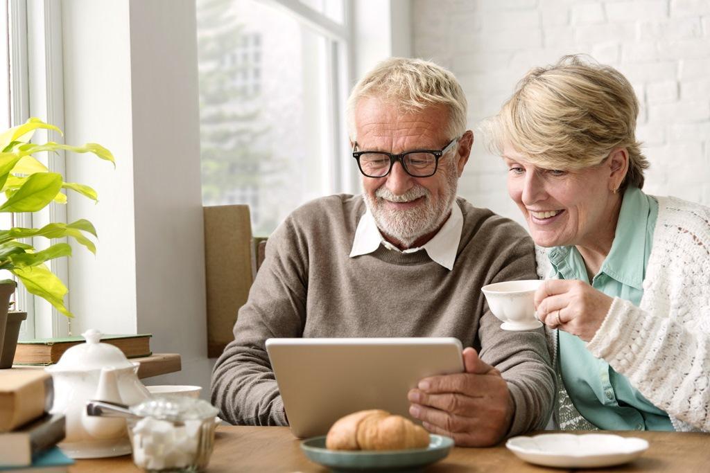 Seniorimies ja seniorinainen verkkopalvelun ääressä.