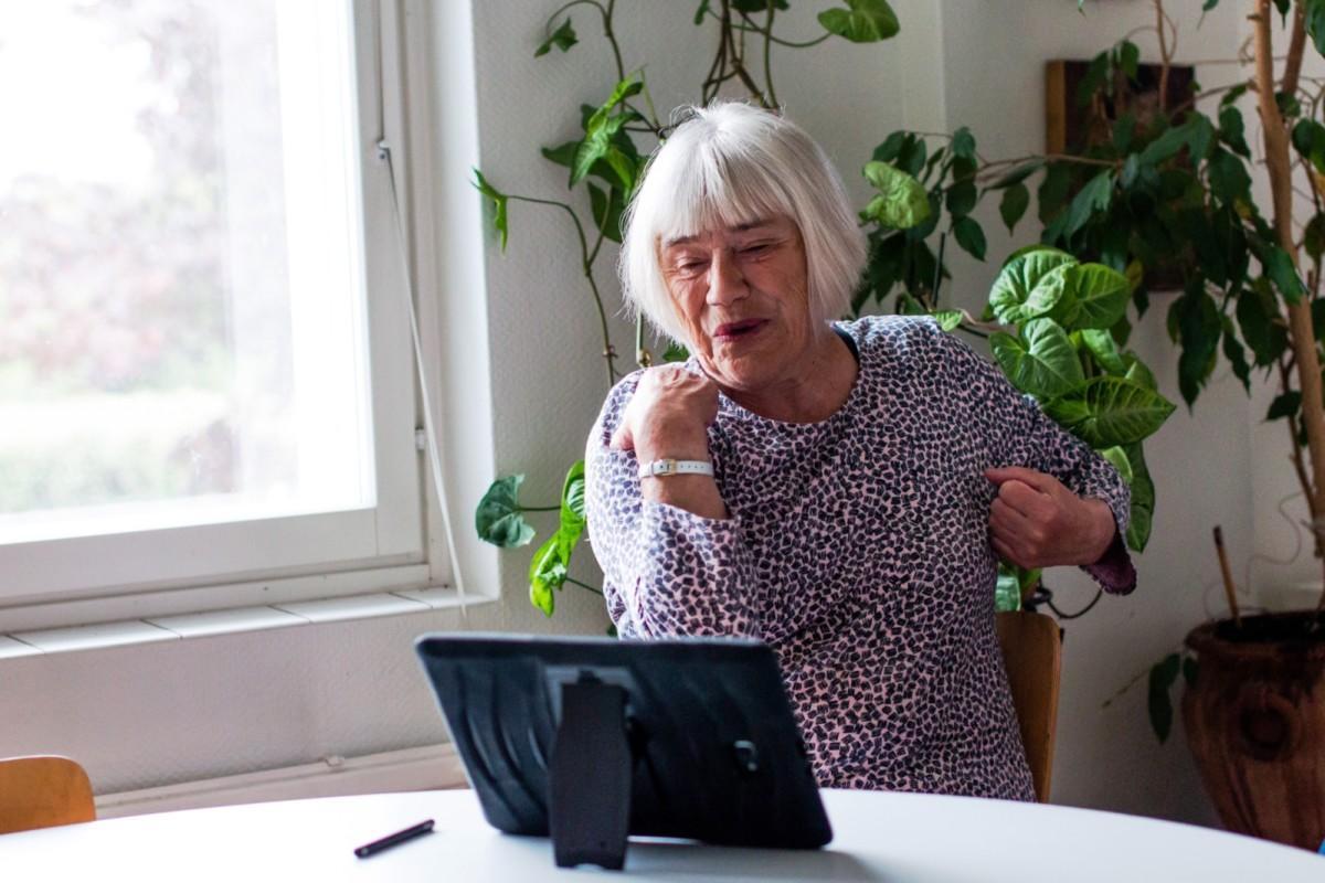 Vanha nainen jumppaa tabletin ääressä.