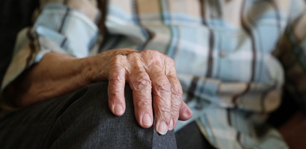 Vanhuksen käsi polvella.