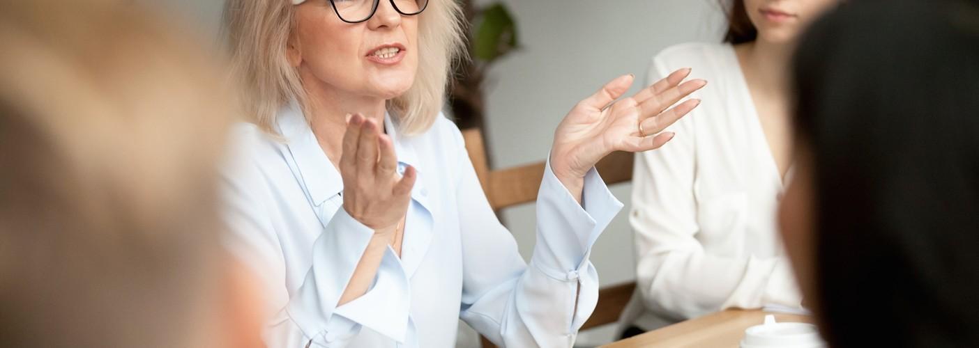 Nainen puhuu kokouksessa.